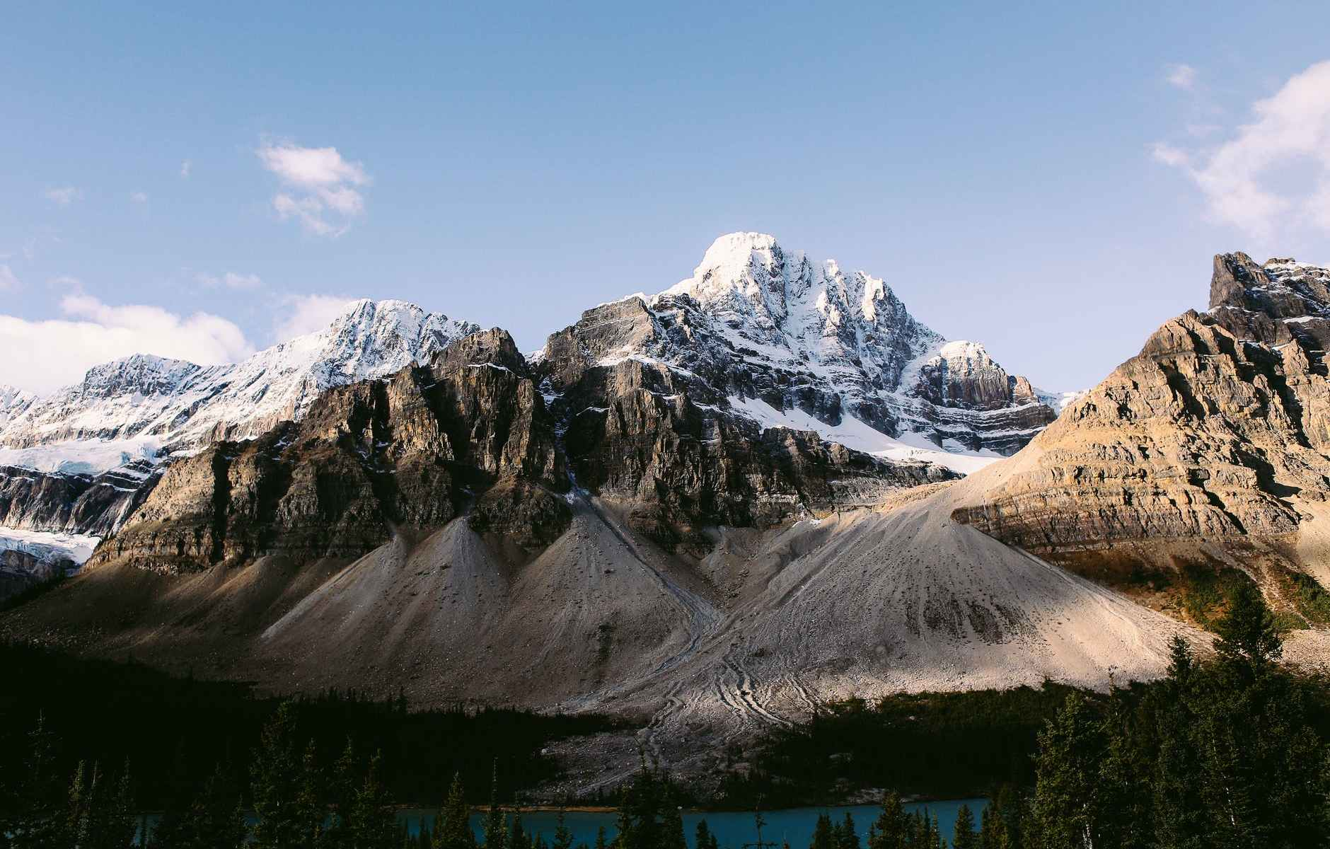 snowy mountain peaks near river and evergreen forest