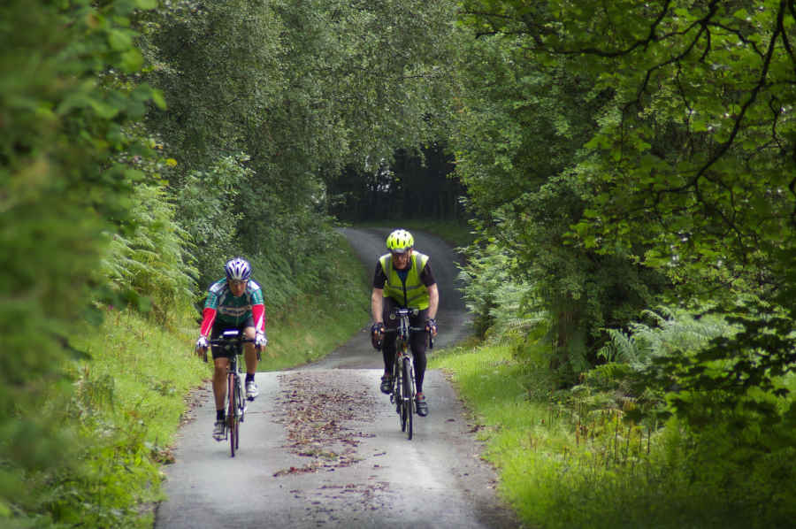 Image of 2 cyclists cycling along leafy lane for Lands End to John O'Groats Cycle Route website home page