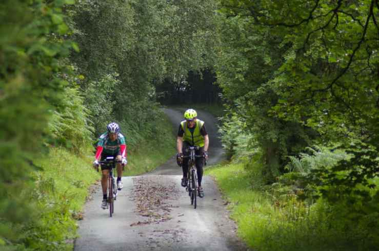 Image of 2 cyclists cycling along leafy lane for Lands End to John O'Groats Cycle Route websit