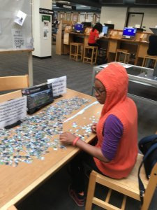 Student working on jigsaw puzzle in library