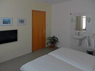 Illustratie: foto van de deur, de bedden en de wastafel van de kamer.