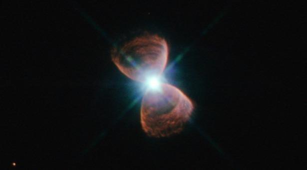 Sebuah planetari nebula bipolar yang bintang asalnya mempunyai semburan dahsyat, yang melontarkan materi dari kutub utara dan selatannya. Kredit: NASA/ESA/Josh Barrington.