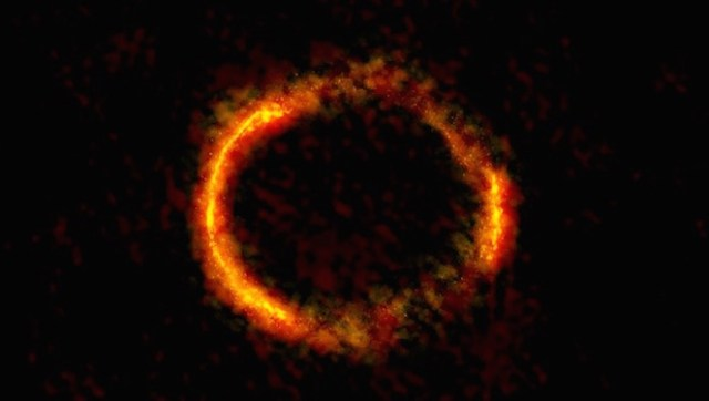 Foto ini dipotret tahun lalu oleh astronom dengan menggunakan teleskop ALMA. Galaksi jauh ini sama sekali tidaklah berbentuk cincin, tapi menjadi bentuk demikian akibat lensa kosmis yang membelokkan cahaya dari galaksi jauh hingga berbentuk cincin. Sama halnya dengan bayangan kita di sendok yang terdistorsi akibat bentuk sendok. Kredit: ALMA (NRAO/ESO/NAOJ); B. Saxton NRAO/AUI/NSF.