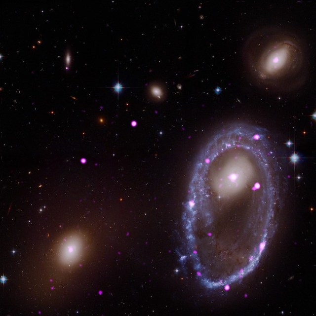 Cincin lubang hitam ini berukuran tiga kali Galaksi Bimasakti. Lubang-lubang hitamnya tersembunyi di dalam pita biru dan pink di sekeliling galaksi di bagian kanan foto. Cincin itu terbentuk ketika sebuah galaksi bertabrakan dengan galaksi lain. Kredit: sinar-X: NASA/CXC/INAF/A. Wolter et al; Optik: NASA/STScI.