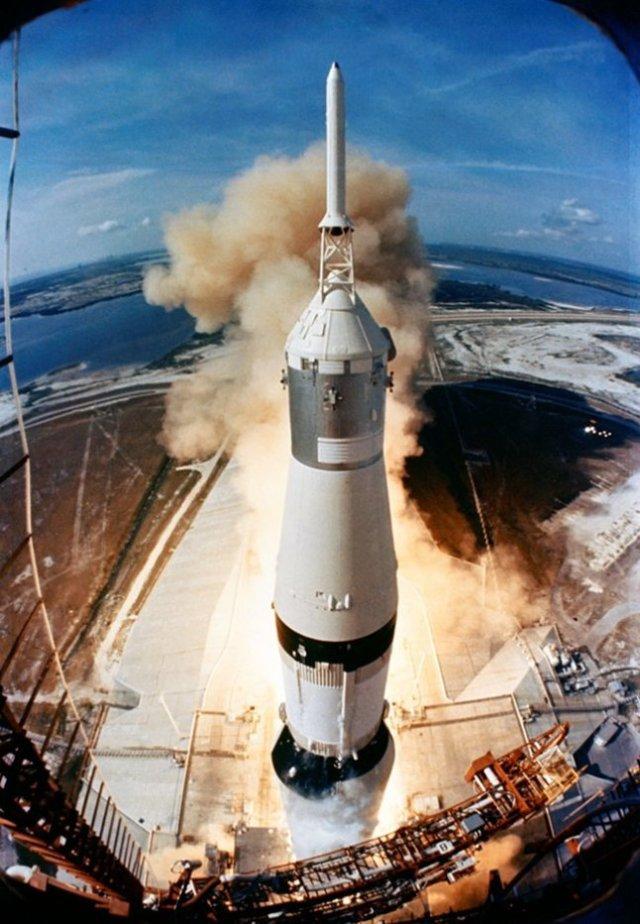 Gambar 1. Pemandangan langka saat roket raksasa Saturnus 5 saat mulai mengangkasa dari landasan peluncuran no. 39A di pusat antariksa Kennedy, Tanjung Canaveral, Florida (Amerika Serikat) pada 16 Juli 1969 TU, diabadikan dari menara peluncuran. Bagian paling atas adalah menara penyelamat, tersambung langsung dengan modul komando wantariksa Apollo 11. Dibawahnya terdapat modul layanan yang berwarna keperakan. Sementara modul pendarat Bulan tersimpan aman dalam sungkup pelindung berbentuk kerucut terpancung, tepat di bawah modul layanan. Sumber: NASA, 1969.