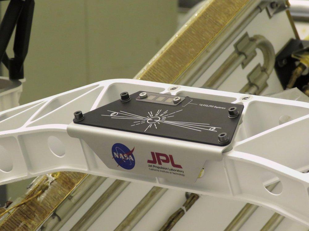 Plakat dengan mikrocip yang memuat nama-nama dari Bumi. Kredit: NASA/JPL-Caltech