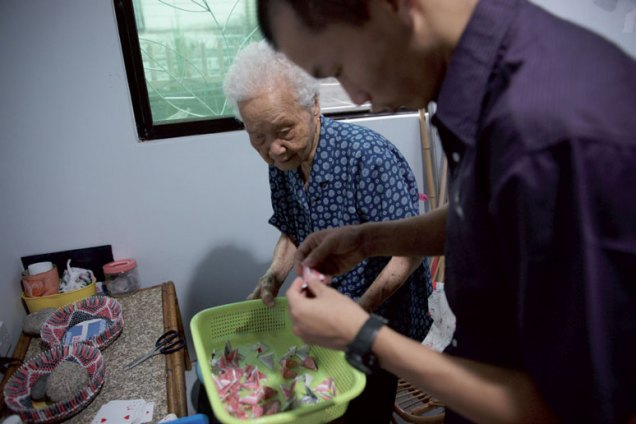 Voon Kun Ying [left] showing Christopher Liew how to make origami flower pots at her house, Kota Kinabalu, 19 May, 2011. Photo © Lonny Pang