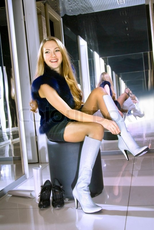 beautiful girl fits on a white boots in stock image