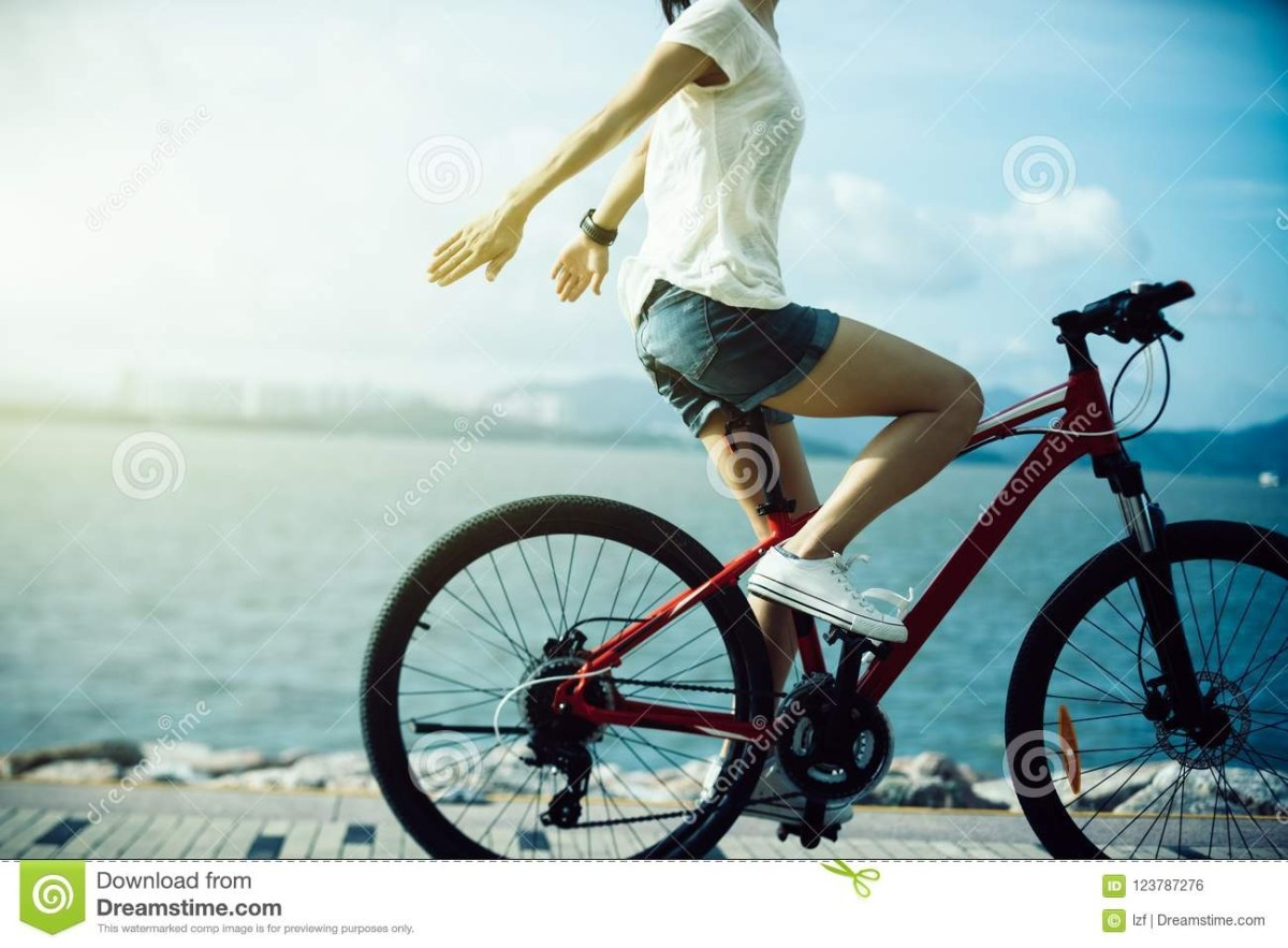 woman riding a bike on sunny seaside stock photo image