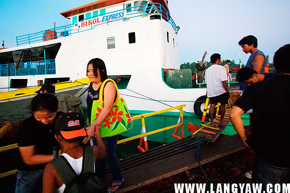 A passenger walks a series of wooden pathways across another boat to board her vessel.
