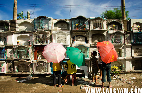 Day time at the Calamba Cemetery and people are already streaming in that it can become chaotic and lively. Here, visitors offer prayers, candles and flowers to their departed.