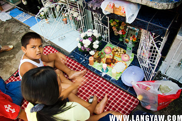 Food offerings for the dead: fruits, rice, viand and a bottle of water are carefully placed infront of a niche.