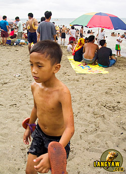 Freshly out of the water, a boy marks the end of Semana Santa at the beach in Talisay City.