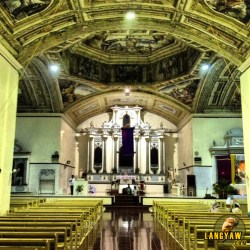 An almost empty church. During the Holy Week, religious sculptures are covered with a cloth