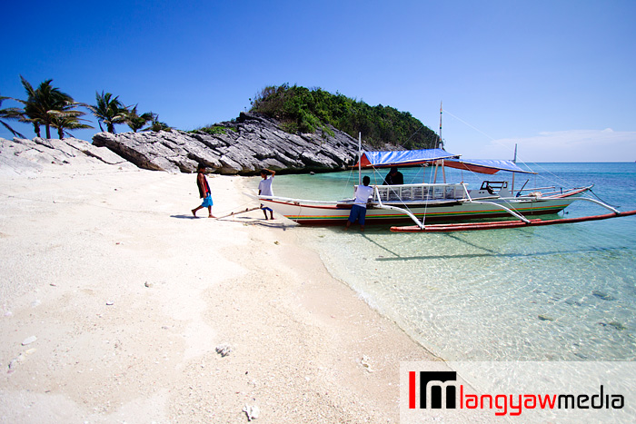 White sandy beach and the rented motorized outrigger boat that took me around Isla Gigantes