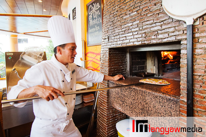 The chef readying a pizza at the mango wood fired oven