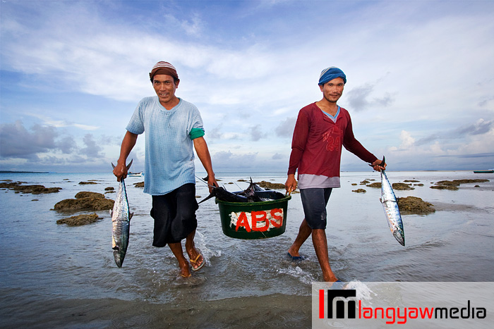 Fishermen carrying fresh catch in the morning off the beach of Cuyo town in Palawan