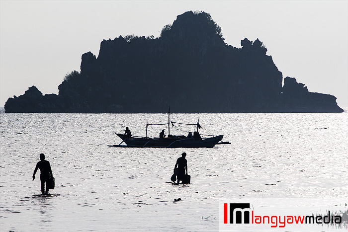 Silhouettes of fishermen, banca and an islet off the coast of Isla Gigantes Norte in Carles, Iloilo