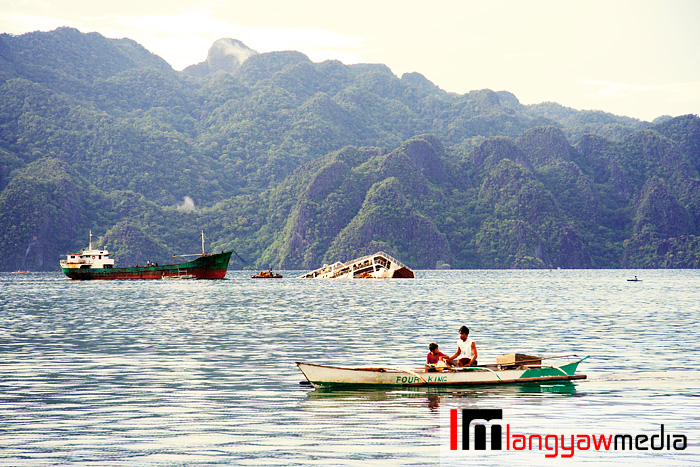 A fisherman passing by boats with Coron's interesting mountains in the background