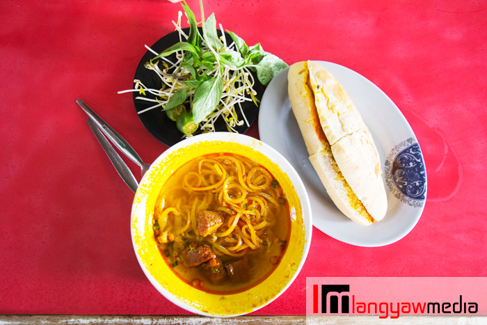 An order of beef stew noodles, pork french bread and a side dish of mung bean sprouts, calamansi and basil leaves