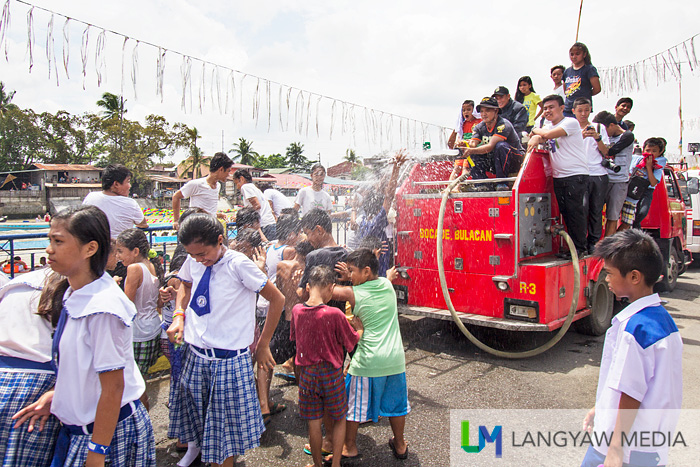 A fireman opens the hose for children. The Pagoda festivity in Bocaue is also an excuse to get wet.