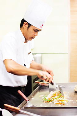 A teppanyaki chef preparing one of the dishes