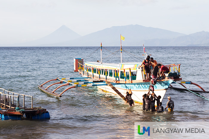 A motorcycle being hauled up as cargo into the outrigger boat