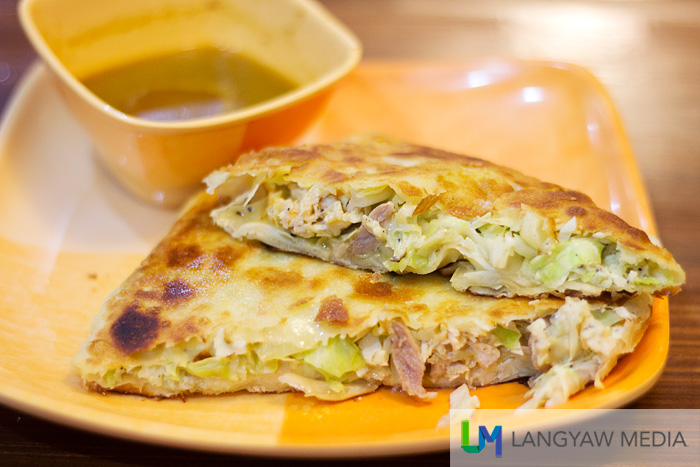 Murtabak ayam is roti filled with cabbage, onions and chicken with curry sauce