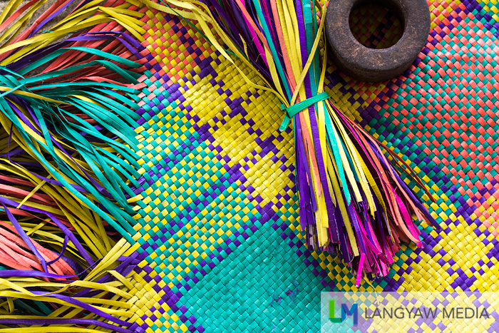 Multicolored strips of pandan and a metal weight the weaver will use to hold the strips