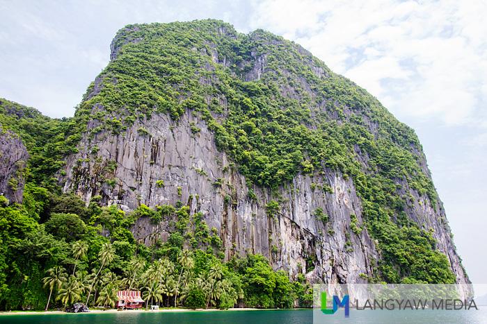 A massive stone cliff dwarfs a quaint hut with a little white strip of sand below
