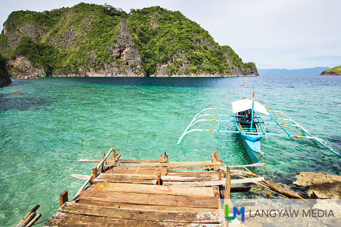 Weathered dock, karst hill, an outrigger boat and emerald waters