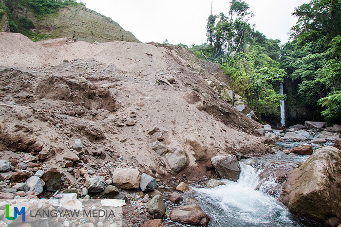 Another view of the excavated soil near the new road. Tuasan Falls in the background.