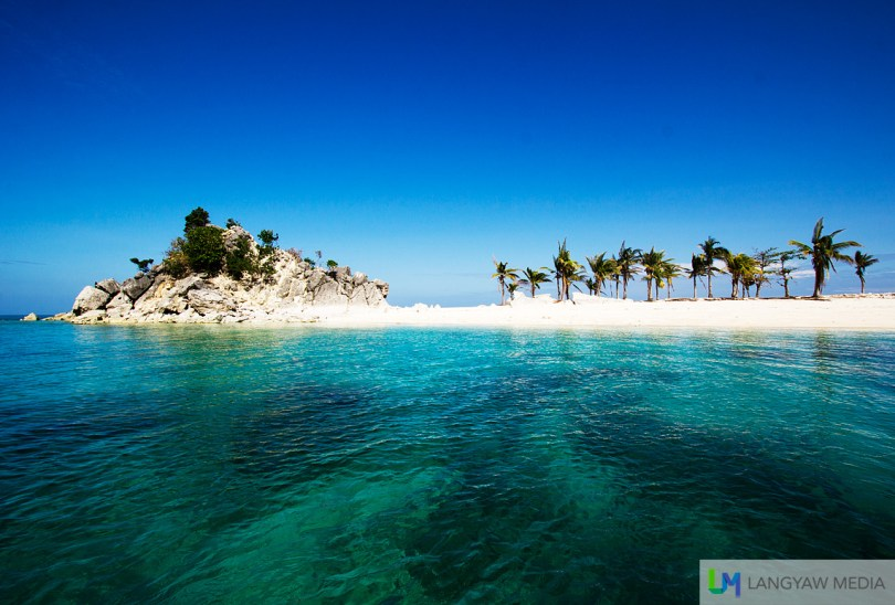 Deep blue waters and blue sky frame the white sand of Cabugao Islet in Isla Gigantes