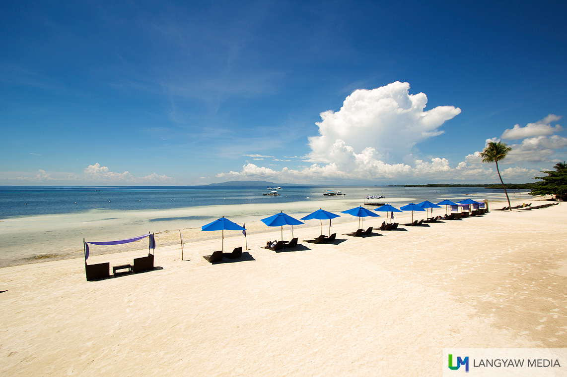 White sand beach and lounging chairs face a tranquil sea