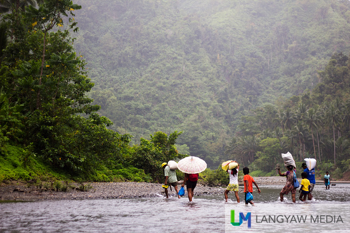 Upper barangay villagers just walk and cross the river despite the wet weather with their goods