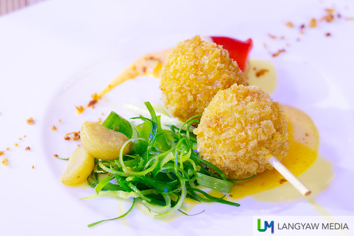 Fried Mac and Cheese shaped into balls and breaded, stuffed with bell pepper. Shredded scallions and garlic confit at the side.