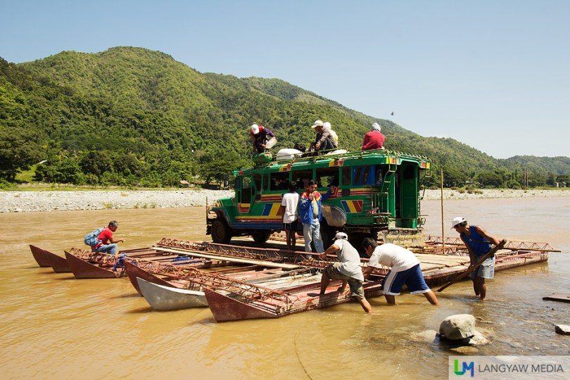 A passenger jeepney going back to Bangued rides the metal raft