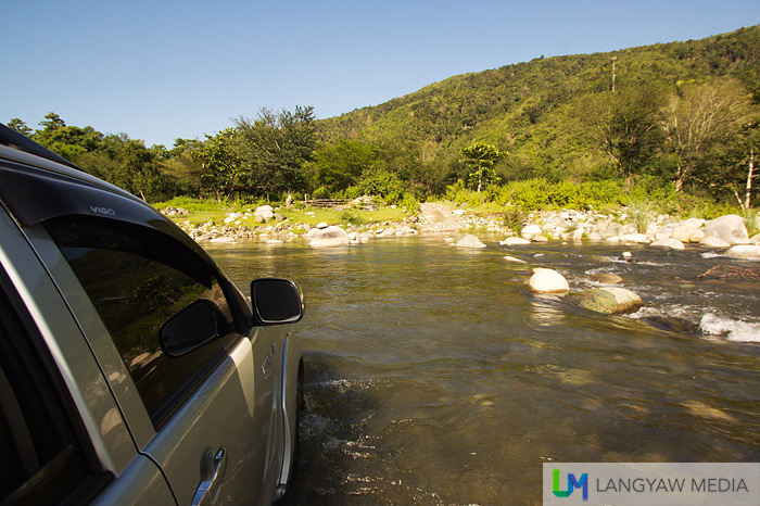 Our offroad vehicle trying to cross the rocky but shallow river