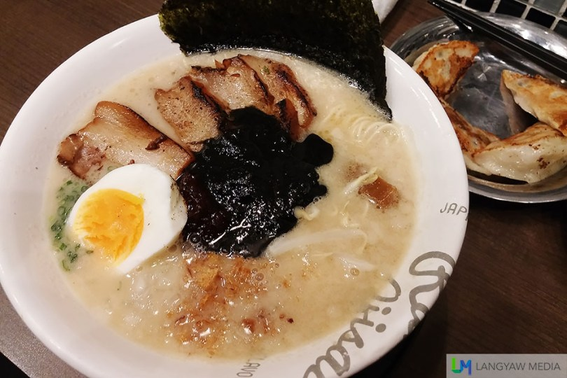 Roast pork ramen black is a soy based soup with stock from long simmered pork bones. It also has menma (simmered bamboo shoots), a piece of nori (seaweed) sheet, moyashi (bean sprouts), a half of tamago (sticky yolk egg) and a black sauce from roasted sesame seeds
