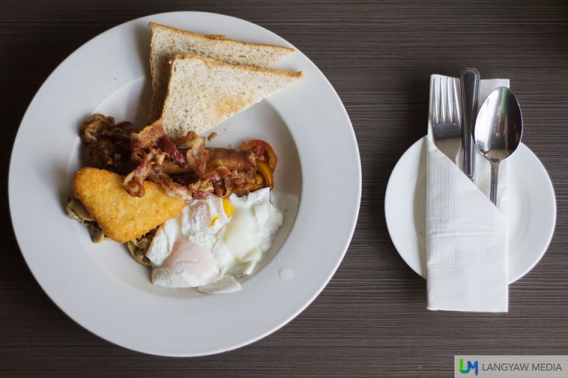Two poached eggs, bacon, aussie beef sausage, tomato and sauteed garlic mushrooms, hash brown and whole wheat bread