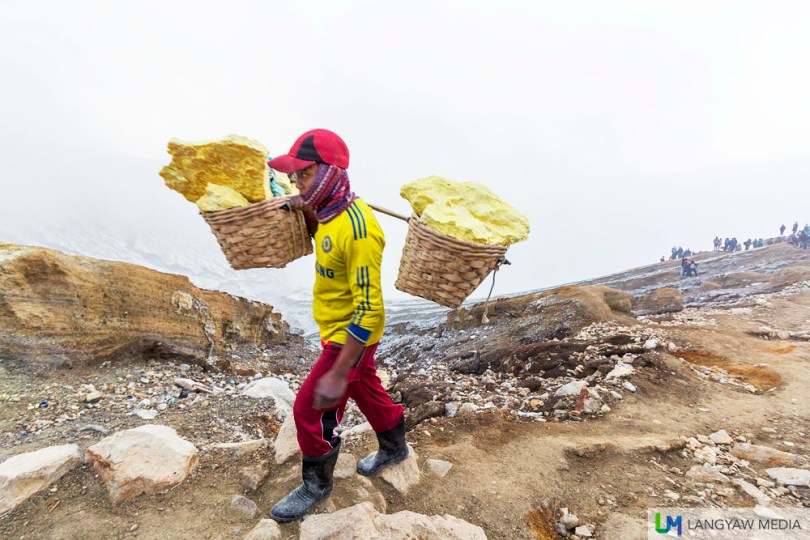 A sulphur miner carrying blocks of the element from the crater below