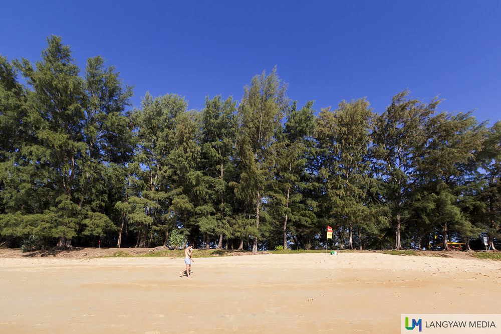 A lone beach goer walking at the beachfront