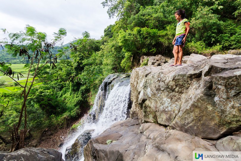 A girl gazes down the top of the waterfall
