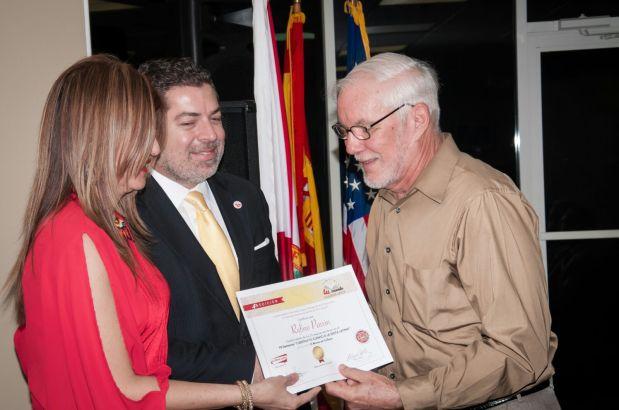 El escritor Rufino Pavón recibe de Marybel Torres y Carlos Montes de Oca su reconocimiento como finalista del concurso.