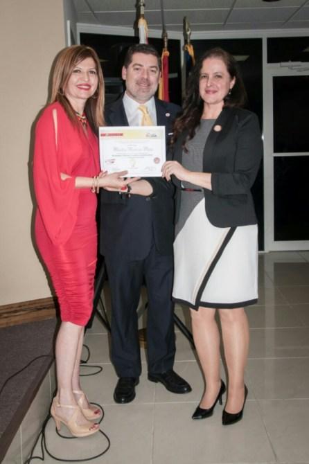 La escritora Maritza Mejía recibe de Marybel Torres y Carlos Montes de Oca su reconocimiento como finalista del concurso.