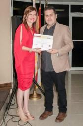 El escritor Lázaro Guzmán recibe de Marybel Torres su reconocimiento como finalista del concurso.