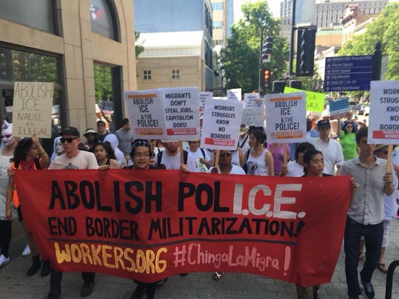 Personas en marcha con una pancarta que dice: abolir a ICE.