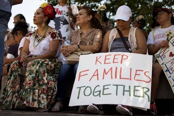 """Mujeres sosteniendo una pancarta que dice, """"Mantengan las familias unidas""""."""