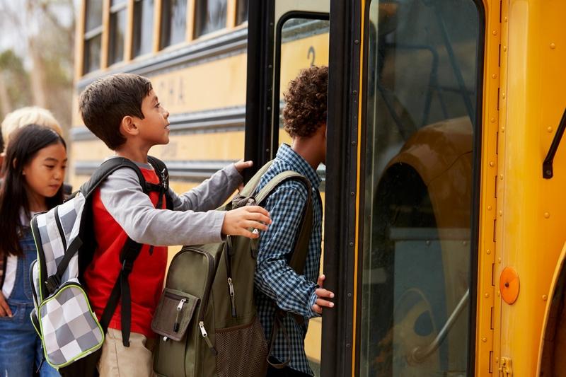 Niños entrando a bus escolar.