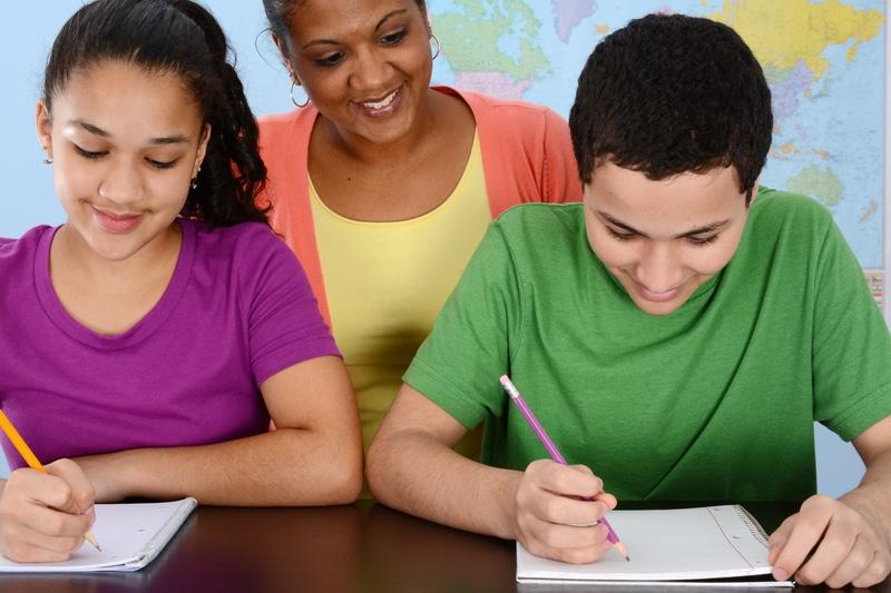 dos estudiantes escribiendo en su cuadernos.